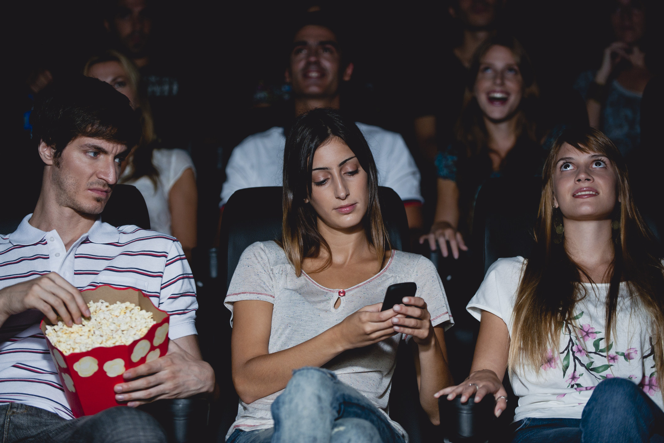 woman on her phone in a movie theater