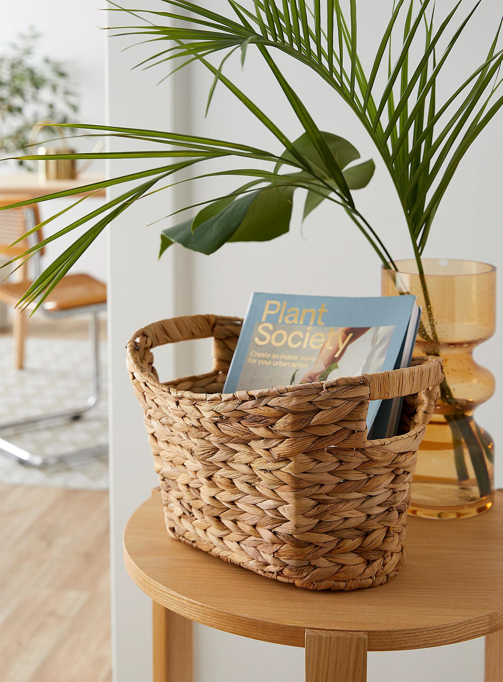 A hand-woven hyacinth magazine basket on a side table
