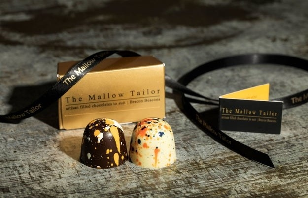 two marshmallow chocolates in front of a gold box and black ribbon