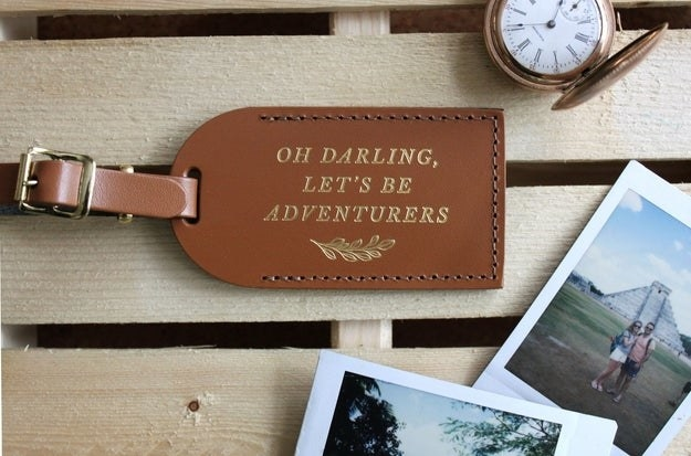 """a brown luggage tag embossed with """"oh darling, let's be adventurers"""""""