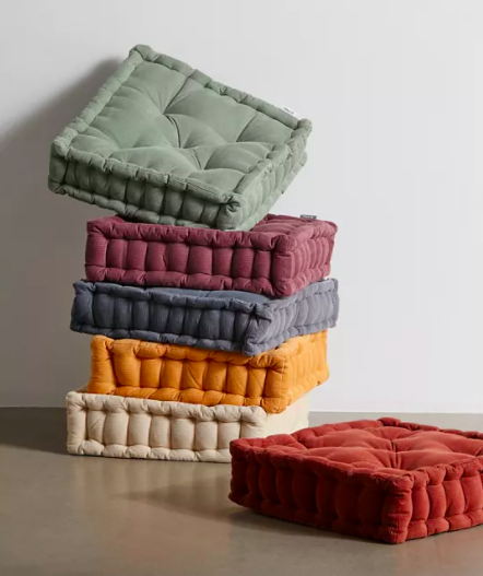 A stack of corduroy cushions in varying colours