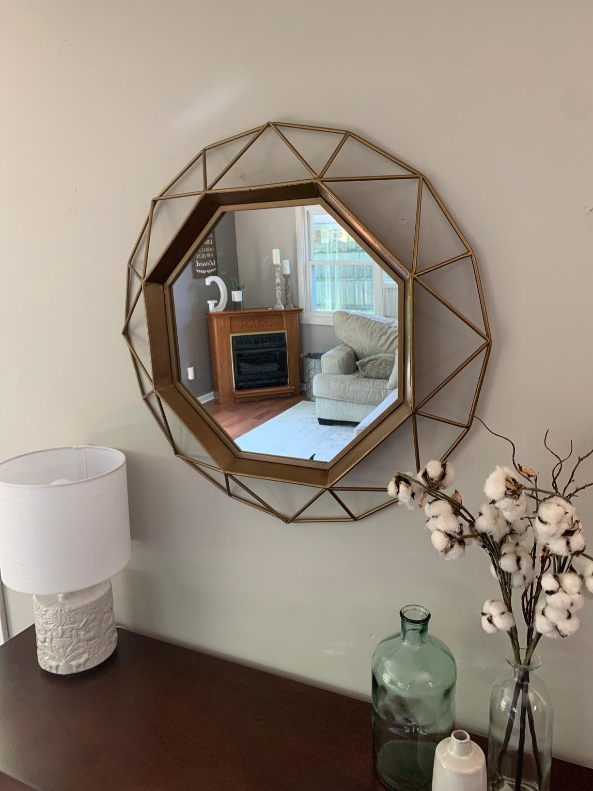 reviewer image of the gold geometric mirror hanging on a wall above a credenza