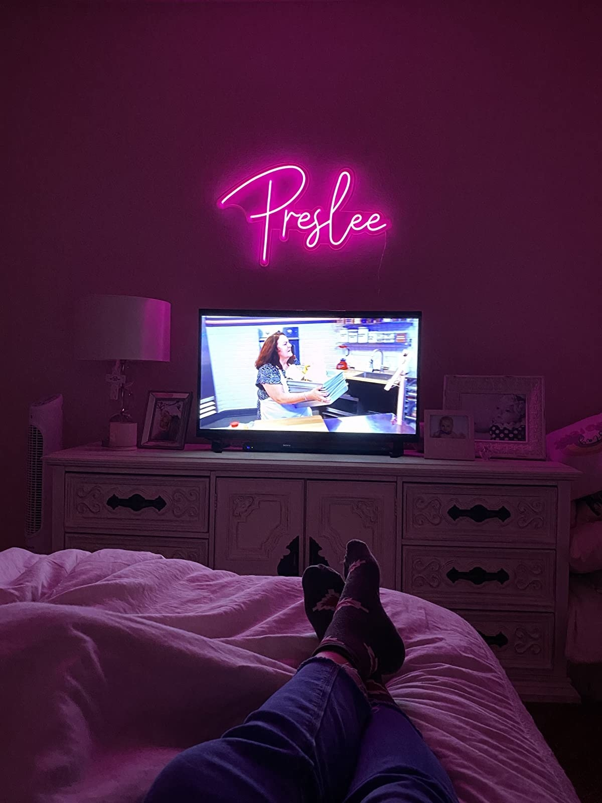 """reviewer image of a pink neon sign that reads """"Preslee"""" hanging on a wall above a TV"""