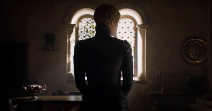 Cersei Lannister stands with her back to the camera in front of two arched windows