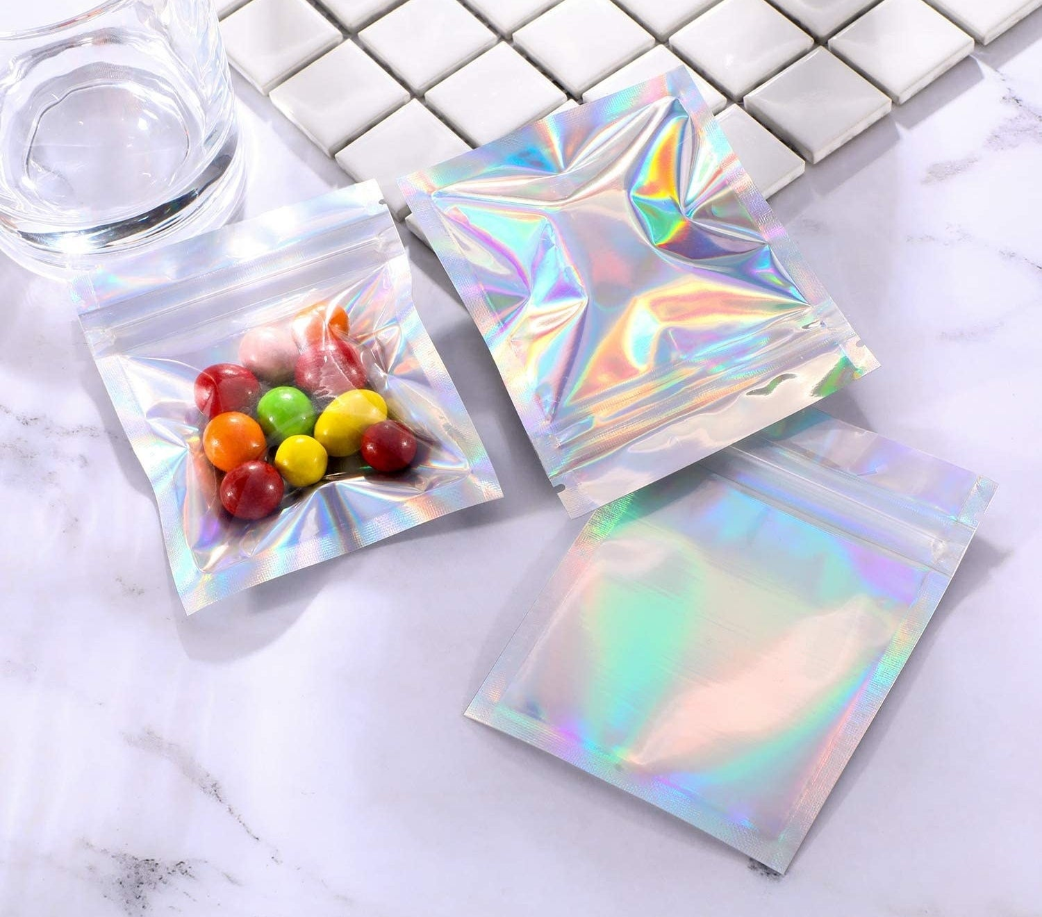 A flatlay of holographic snack pouches containing colourful candy