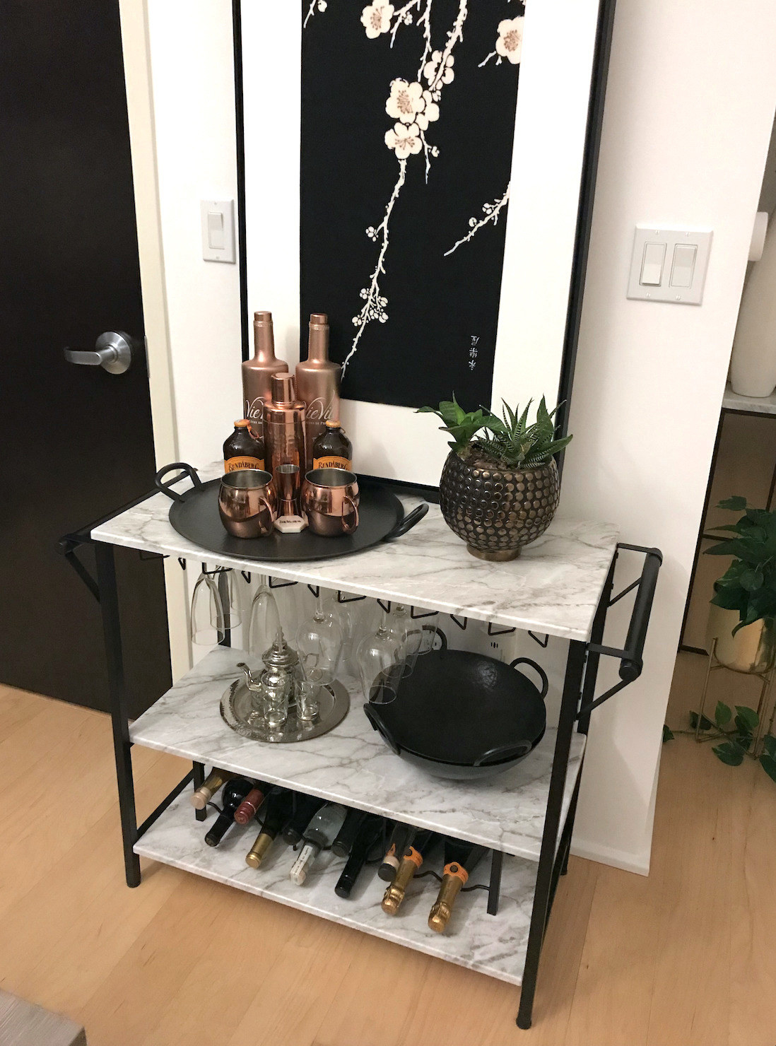 reviewer's bar cart with black bars and white marble shelves