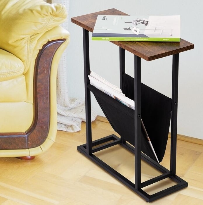 a slim wood-top side table with a black steel base and a black magazine sling