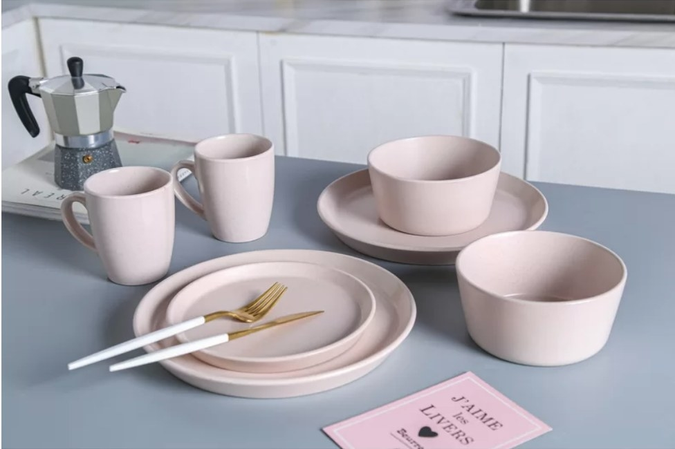 A pink, 32-piece dinnerware set that serves 8 placed on a kitchen island