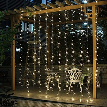 a pergola with ten vertical strands of string lights hanging form it
