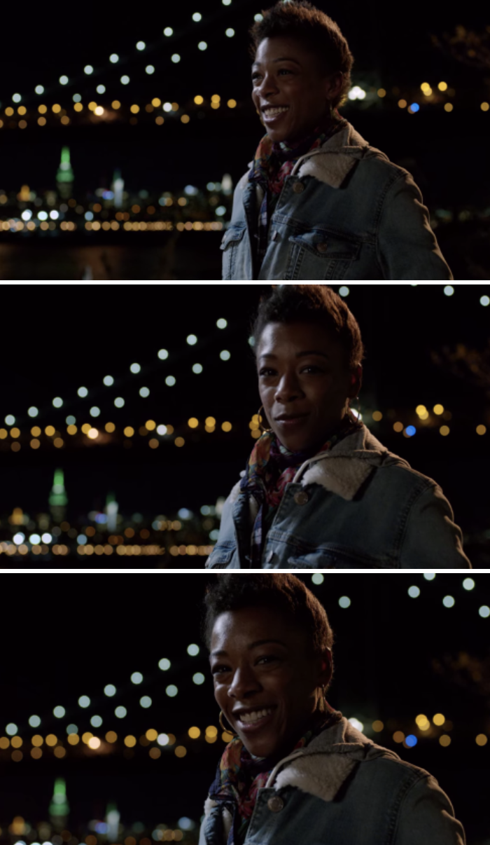 Poussey standing with the city skyline behind her at night, smiling