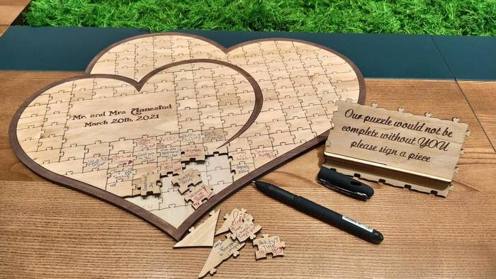 a heart-shaped board with puzzle pieces in side that guests would sign. It also has a part of the heart with no pieces that has the last name of the couple and their wedding date engraved in it