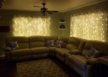 a reviewer photo of the string lights hanging behind sheer curtains in a darkened living room