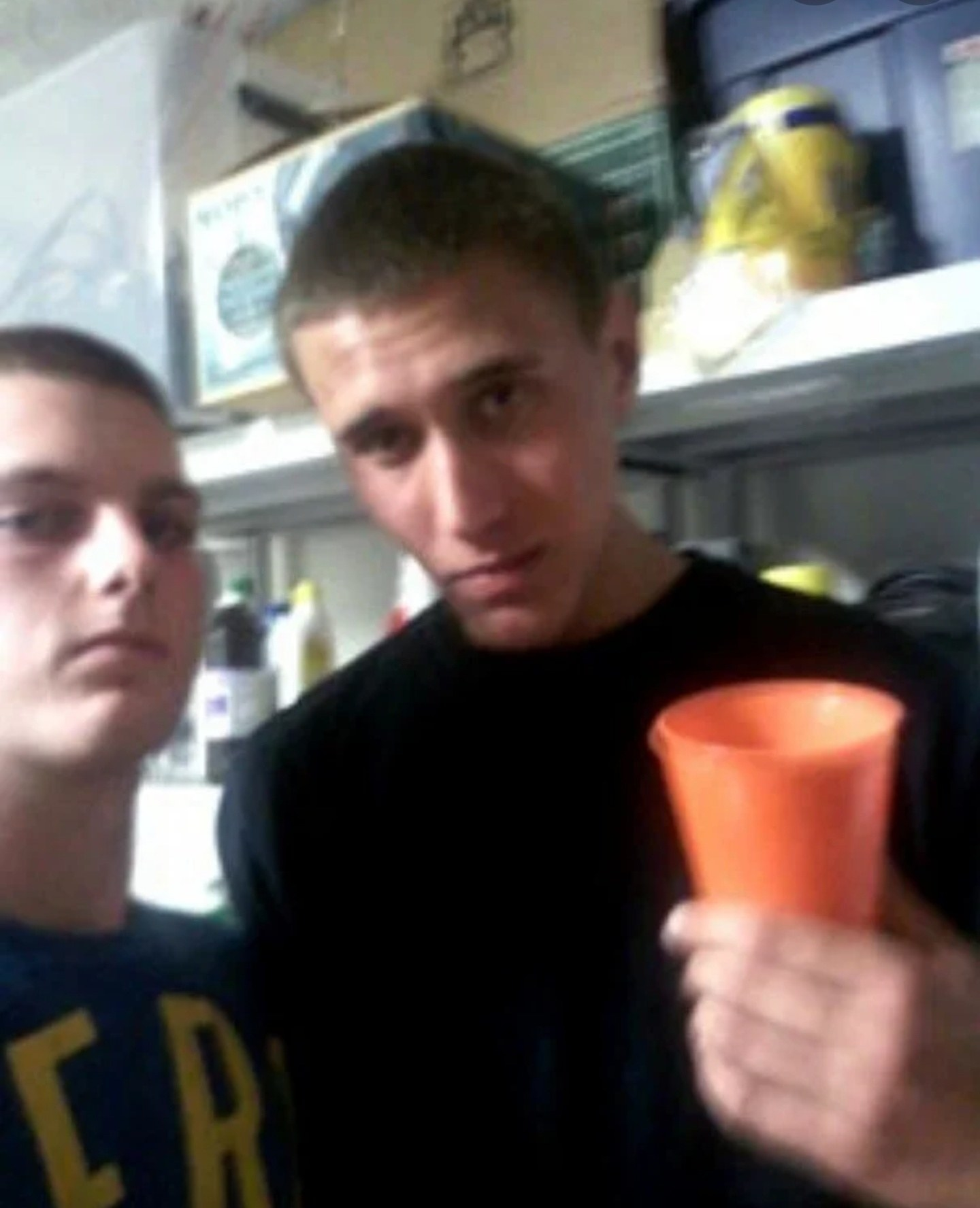 Tyler Hadley holding a cup and posing with his best friend Michael Mandell