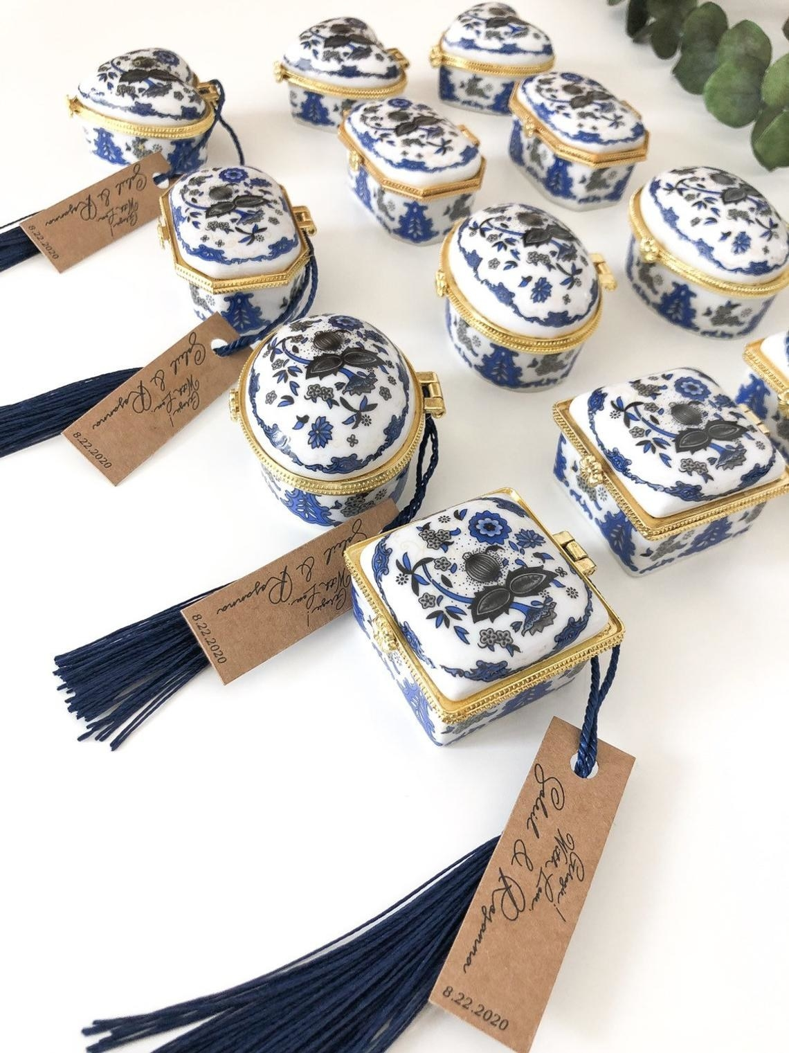 the wedding favor boxes made of the traditional porcelain with the blue floral print with blue fringe tassels hanging from them and a brown card with the name