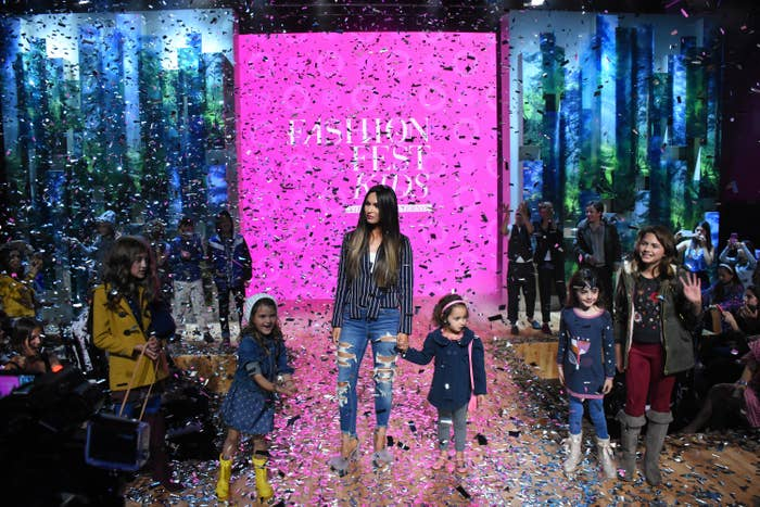 Megan standing on a catwalk with her kids as confetti rains down