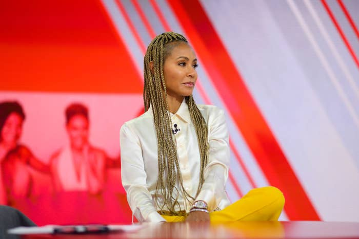 Jada Pinkett Smith sits with her leg crossed on her lap while filming Red Table Talk