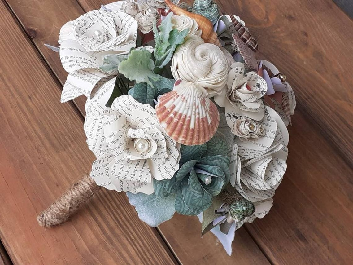 the flower bouquet with seashells and book page white roses with pearls at the cefnter