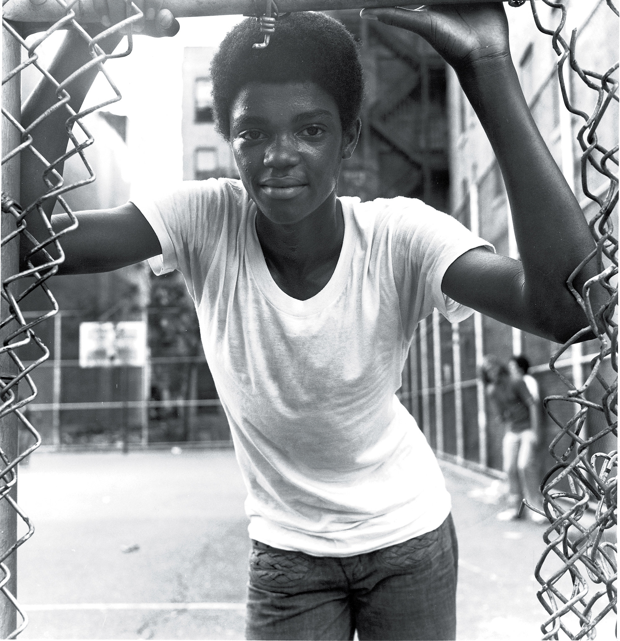 A young Black person smiles and stands by the side of a basketball court while looking through a gap in a chain-link fence