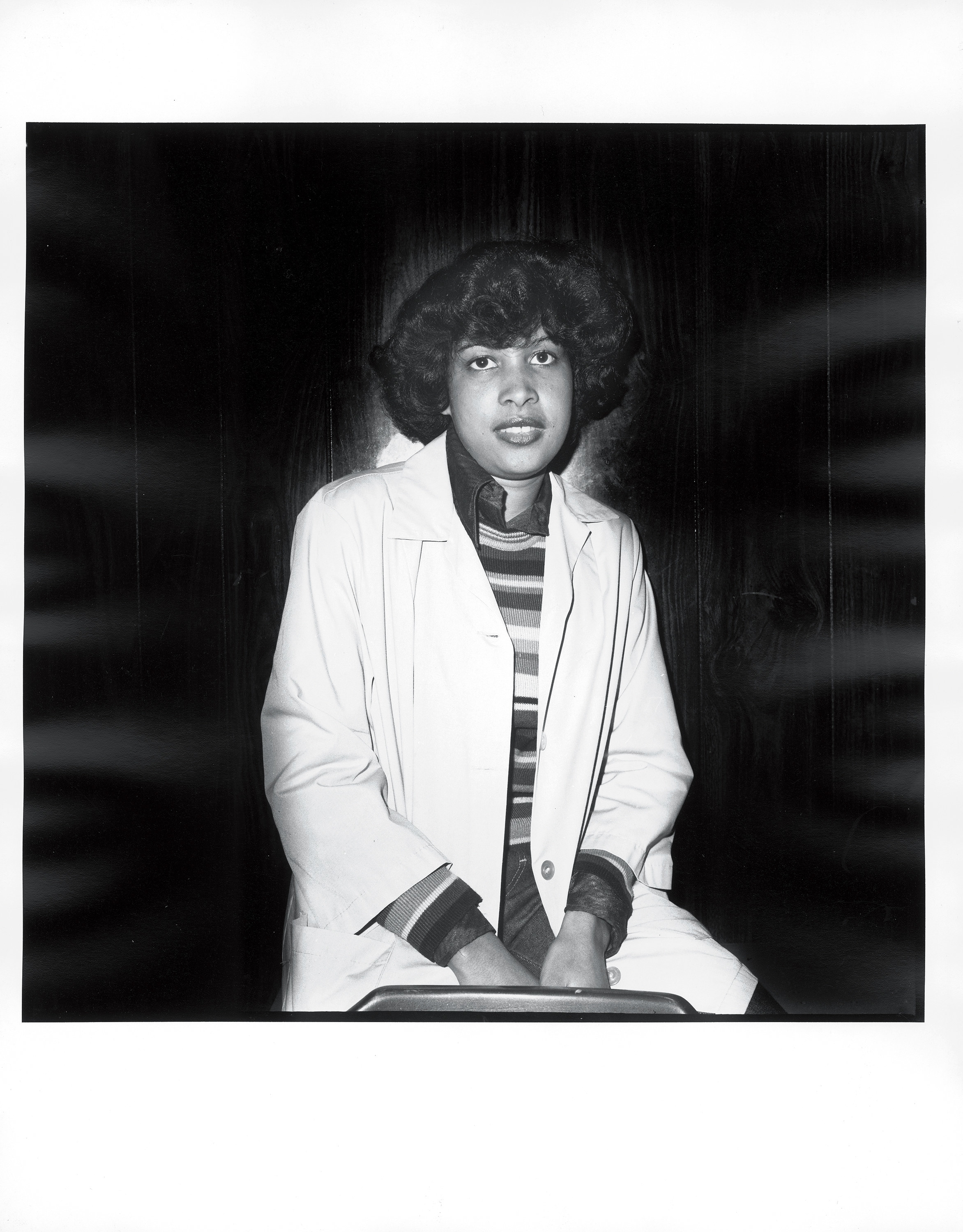 A young woman in a white coat looking directly into the camera