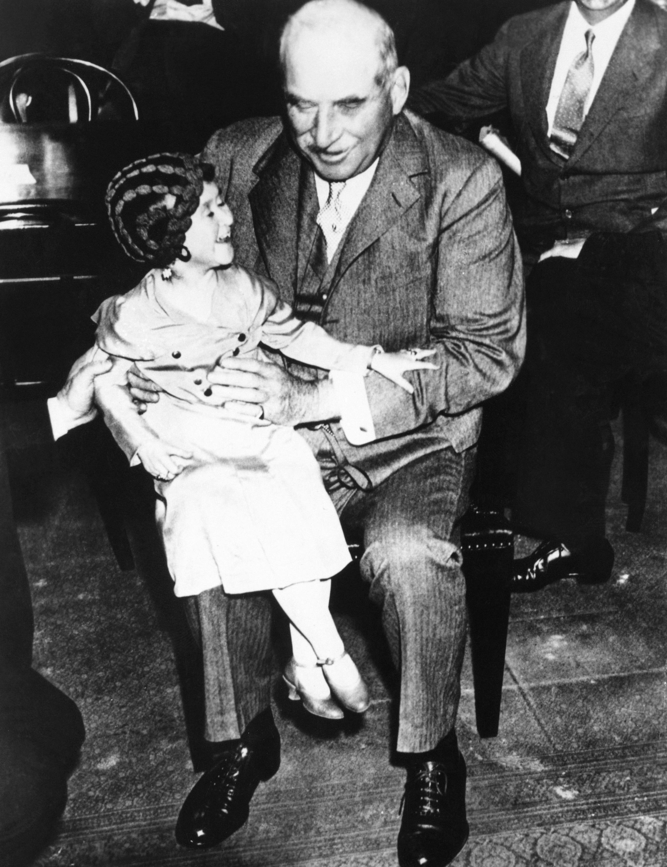 JP Morgan holding Lya Graf in his lap at a Senate Banking Committee hearing