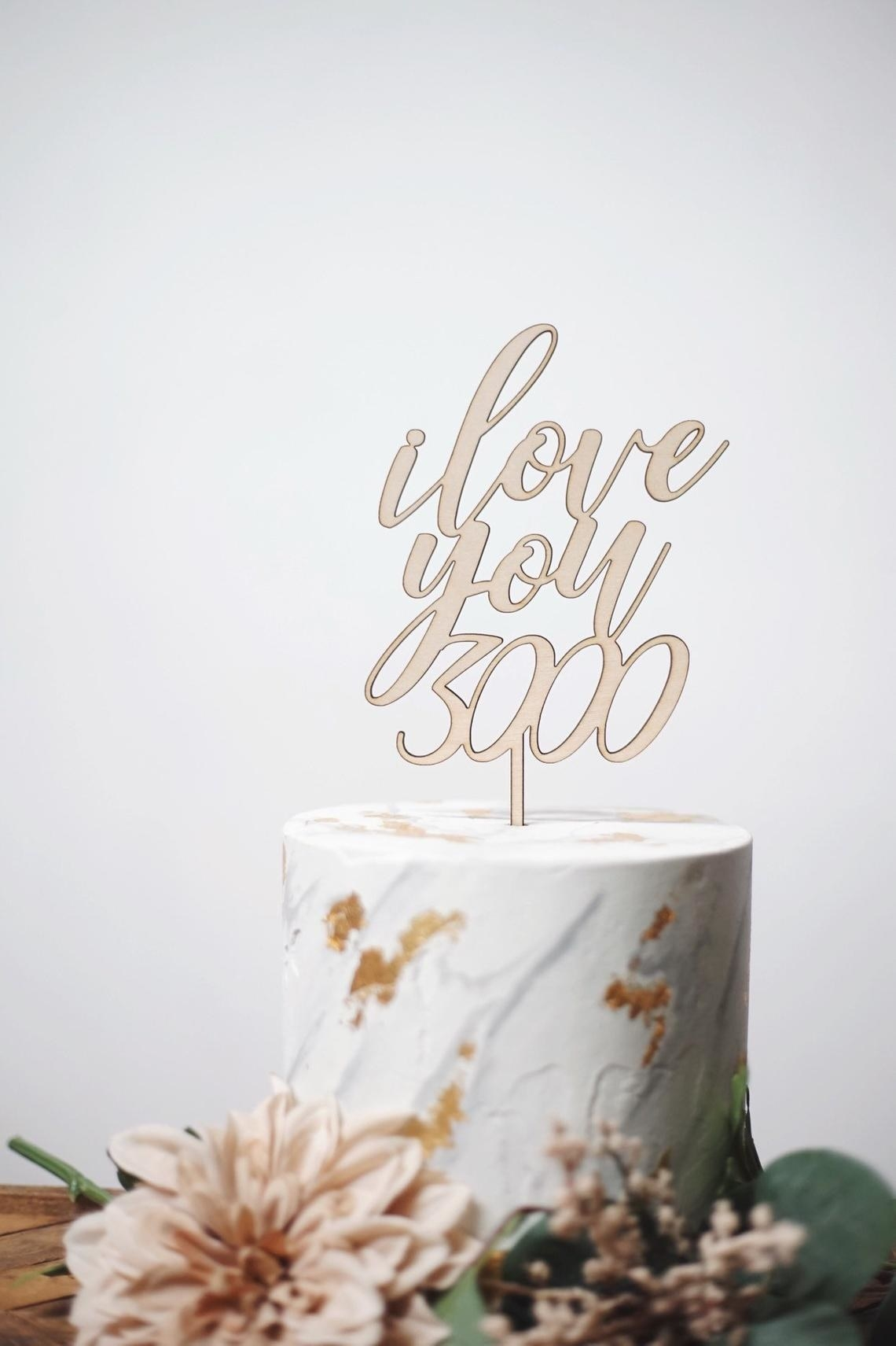 gold cake topper on a marble cake with gold leaf accents and flowers around it