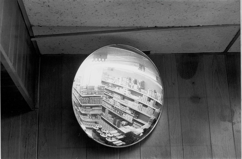 A surveillance mirror showing aisles of goods against a plain wall