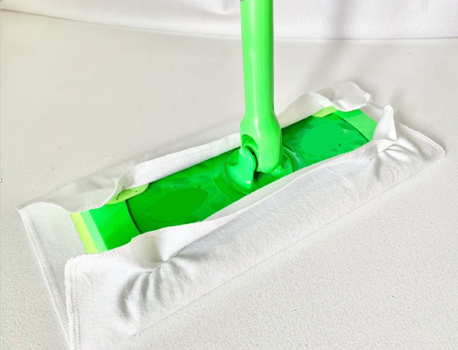 White cotton cover wrapped around a green Swiffer
