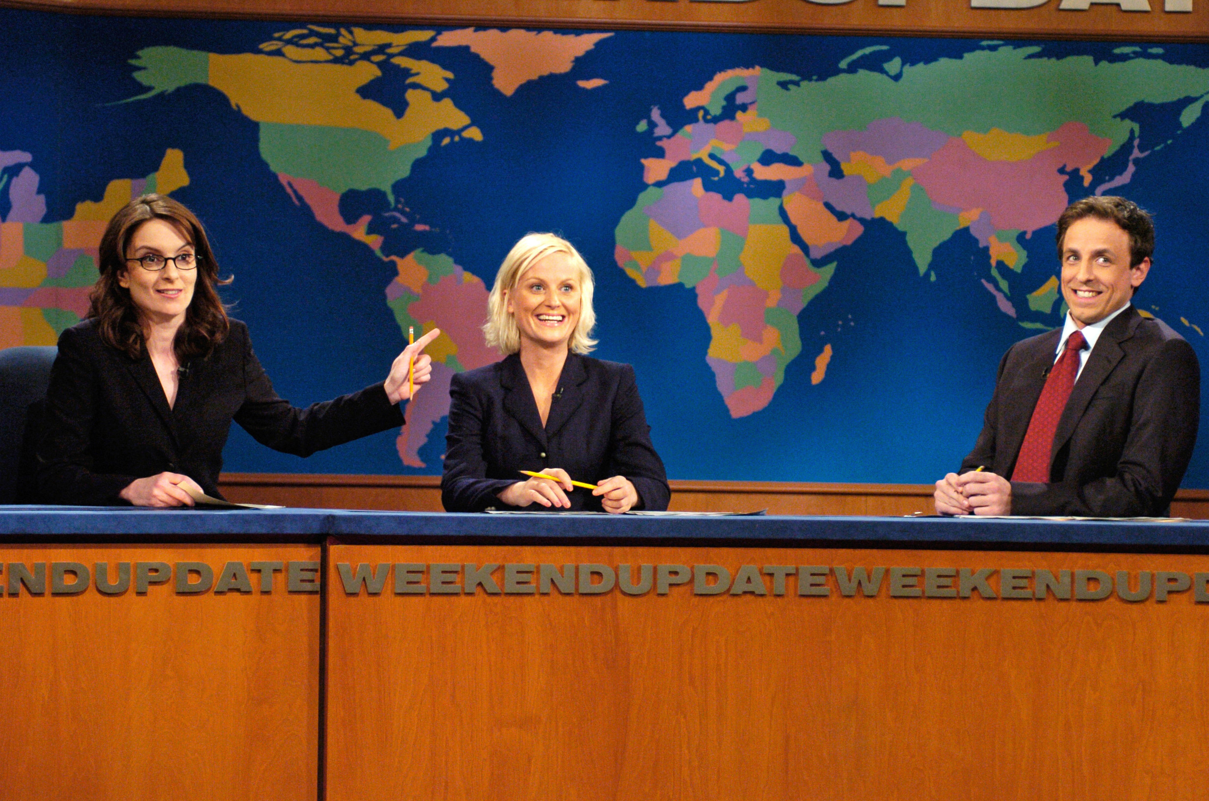 """Tina Fey, Amy Poehler, and Seth Meyers sit at the """"Weekend Update"""" desk"""