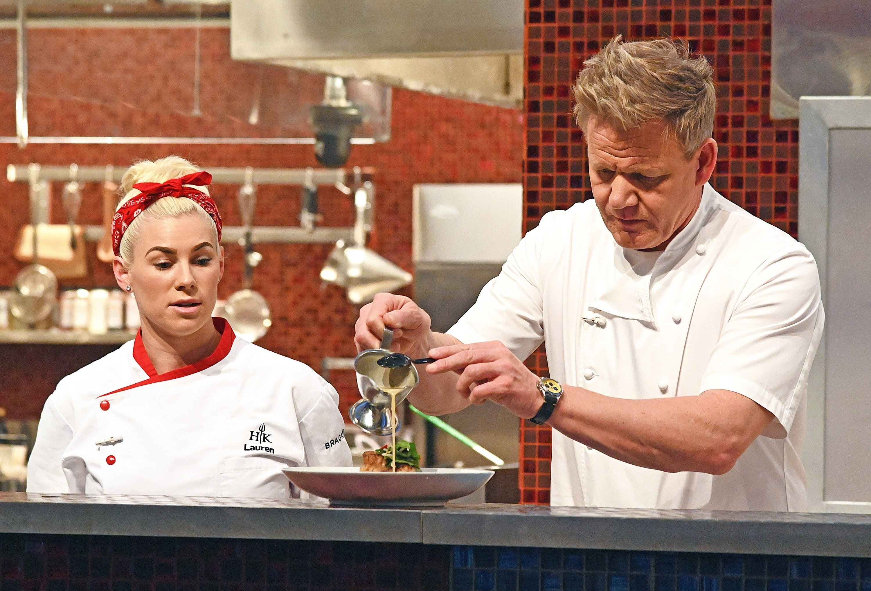 Gordon Ramsay plates a dish while Lauren Lawless watches