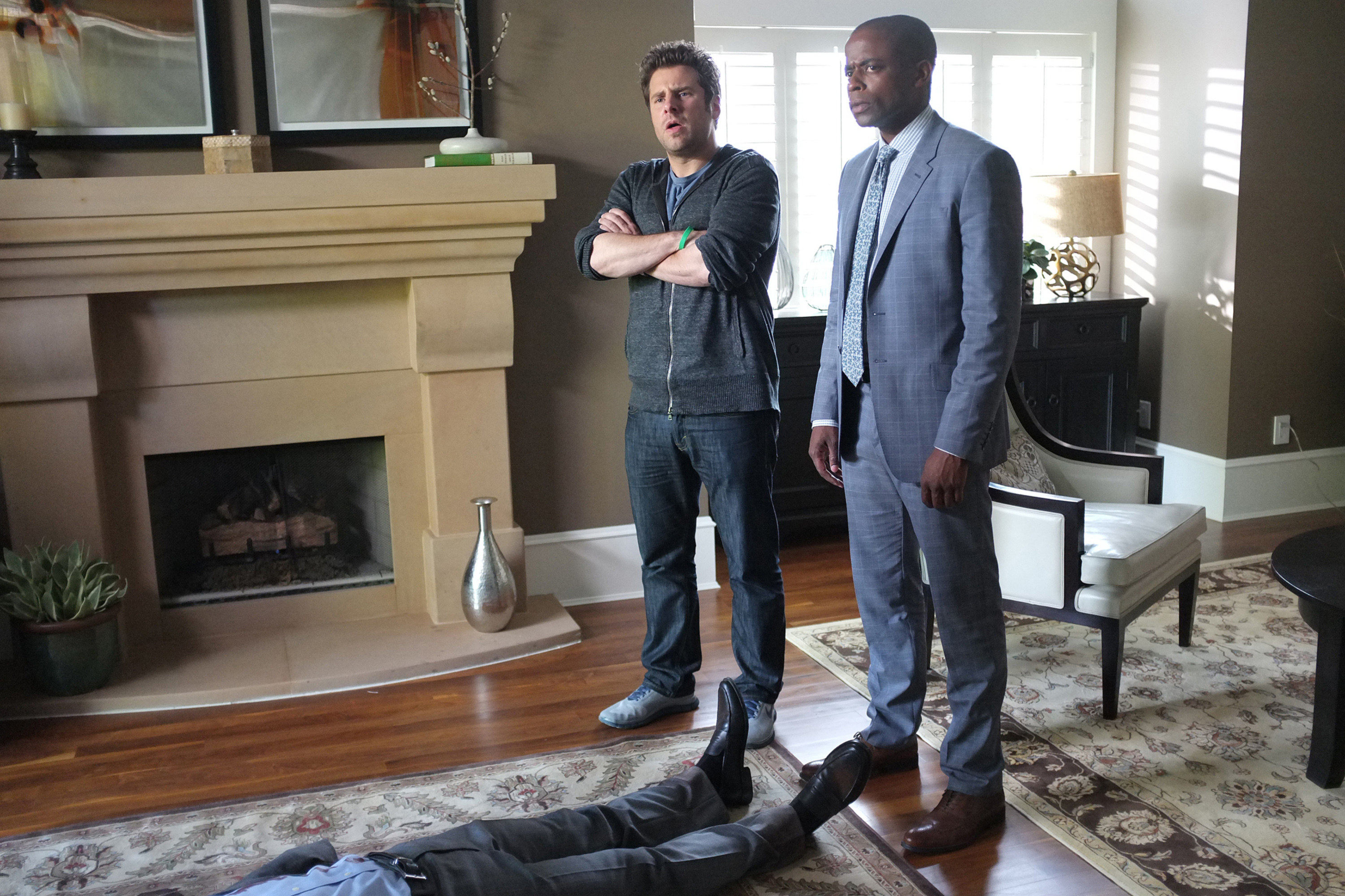 James Roday and Dule Hill stand in a living room over a body