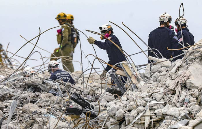 Rescuers wearing masks and helmets stand in the twisted rubble
