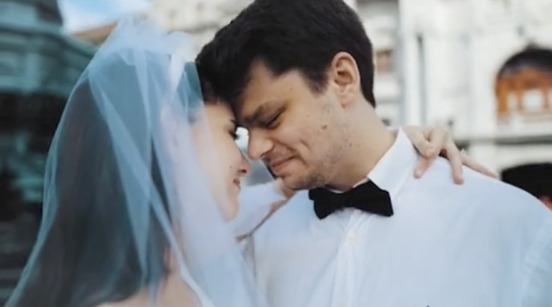 Grace wearing a veil as she embraces Brandon, who sporting a dress shirt and bowtie, on their wedding day
