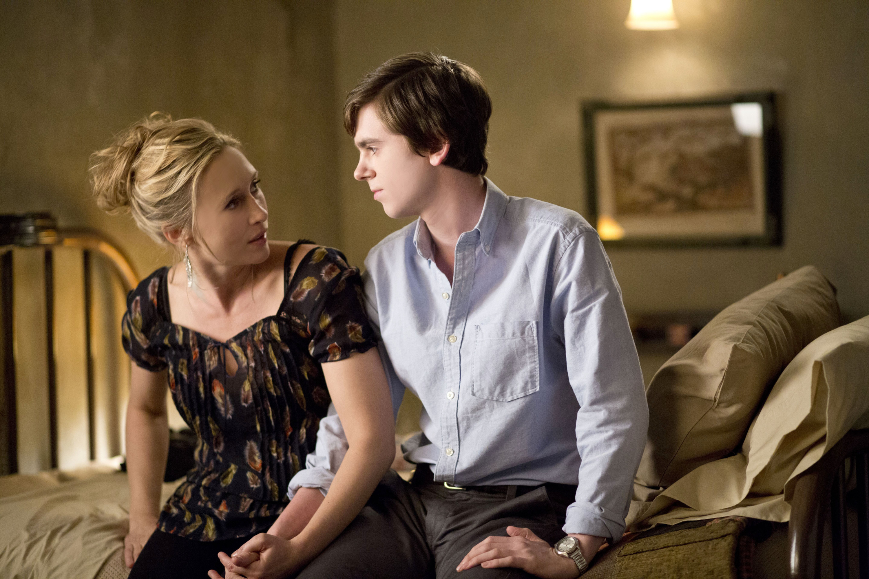 Vera Farmiga and Freddie Highmore hold hands on a bed