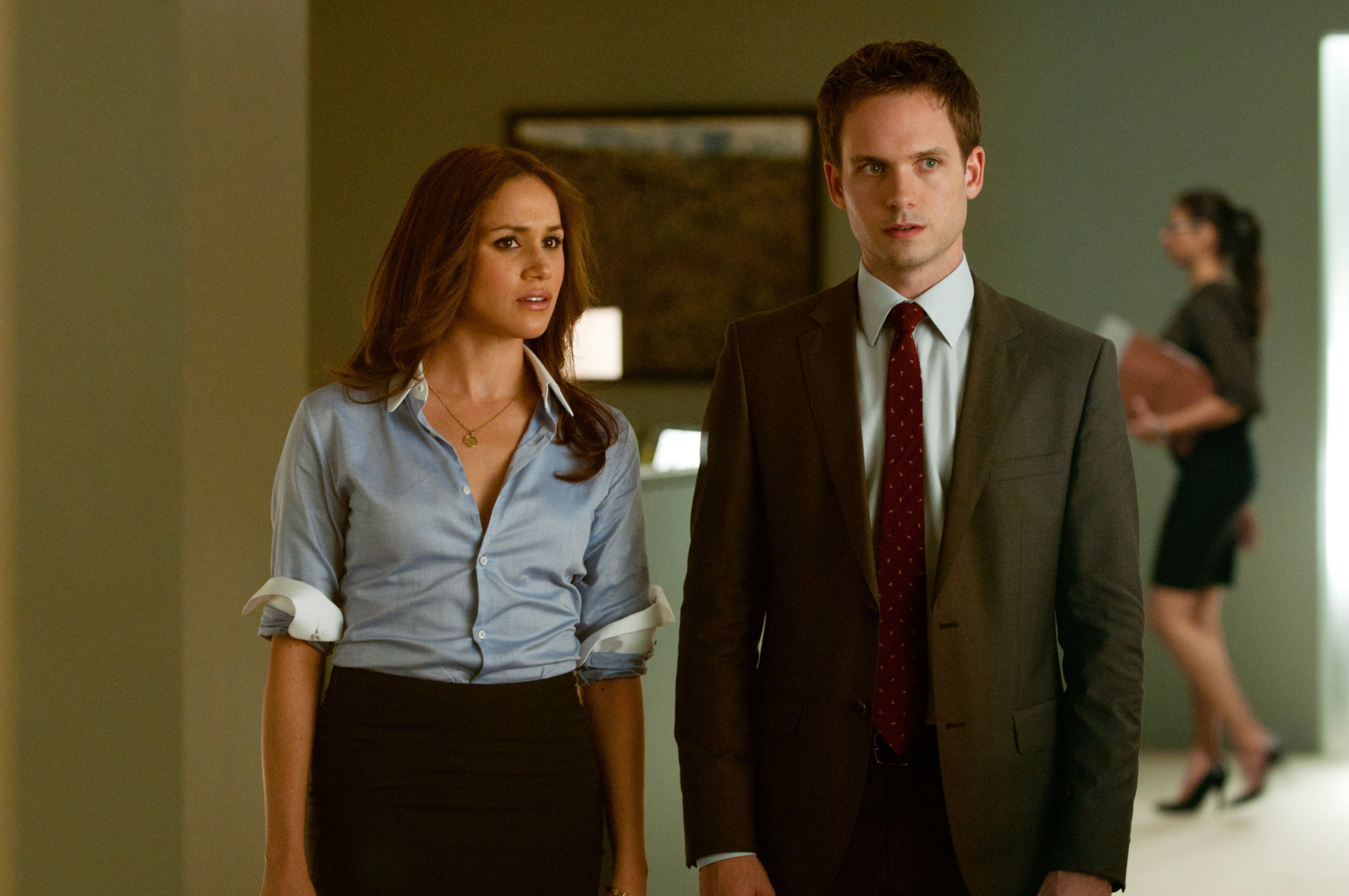 Meghan Markle and Patrick J. Adams stand in a hallway together