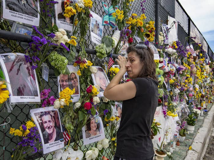 A woman cries in front of a memorial with flowers and pictures of victims