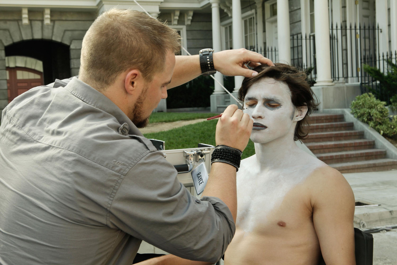 Rayce Bird does makeup on a man