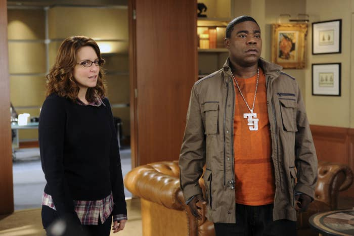 Tina Fey and Tracy Morgan stand in an office