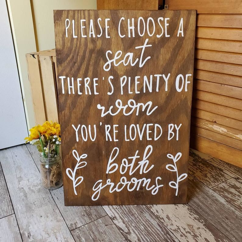 """wooden sign that says, """"Please choose a seat. There's plenty of room. You're loved by both grooms."""" How sweet is that?"""