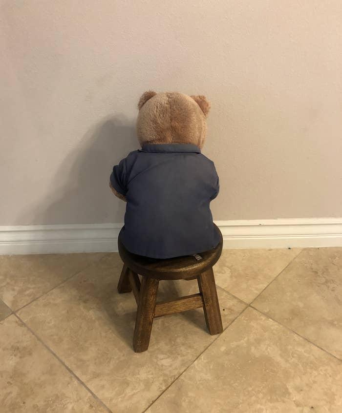 A stuffed bear sits on a stool facing the wall