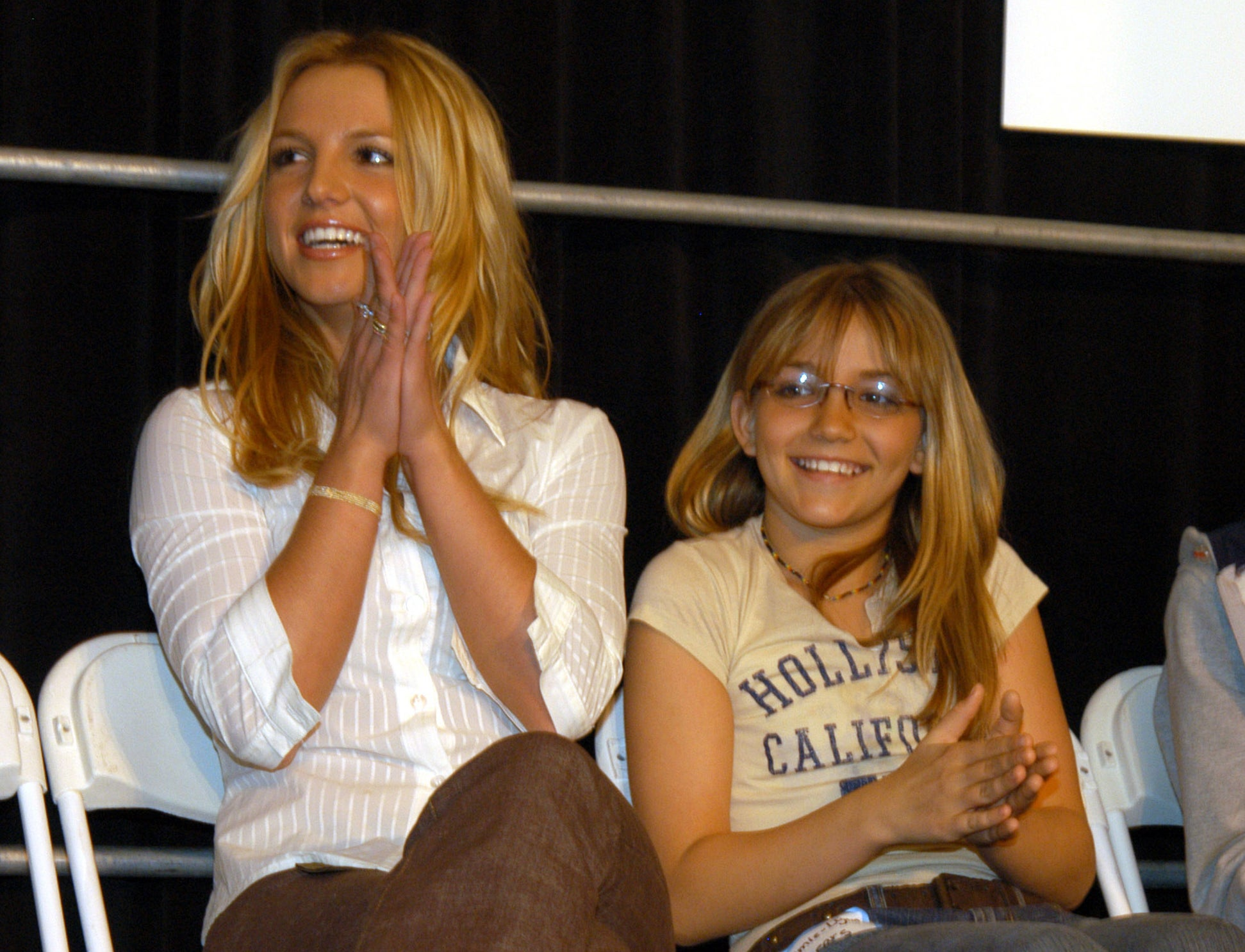 Britney claps while a young Jamie Lynn sits next to her at an event