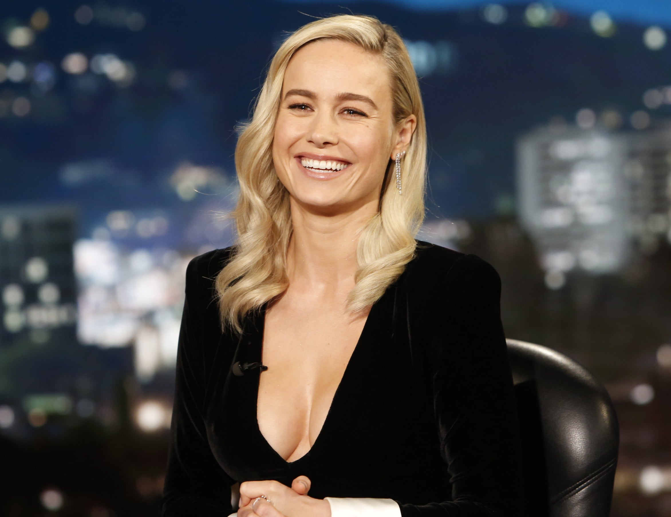 Brie smiles big while sitting and wearing a black dress with a plunging neckline