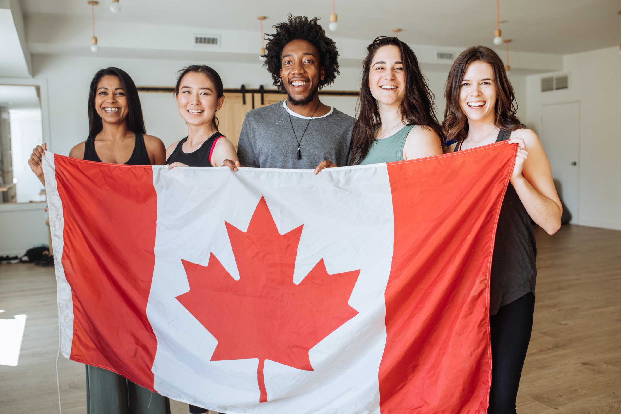Five young people hold up a Canadian flag