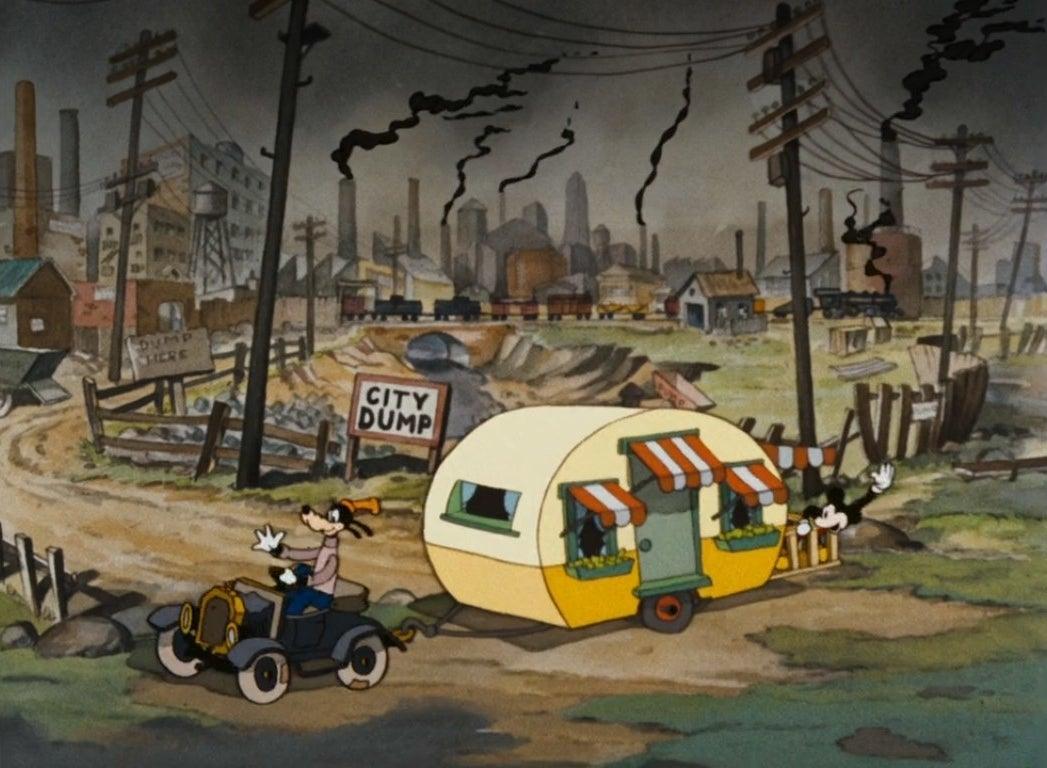 Goofy drives Mickey's trailer away from the city dump
