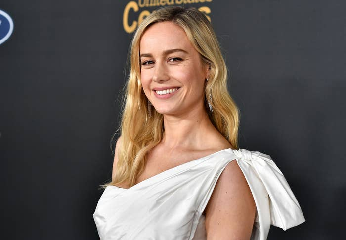Brie smiles in a silver one-shoulder dress at a premiere