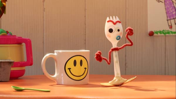 Forky stands next to a smiley face mug
