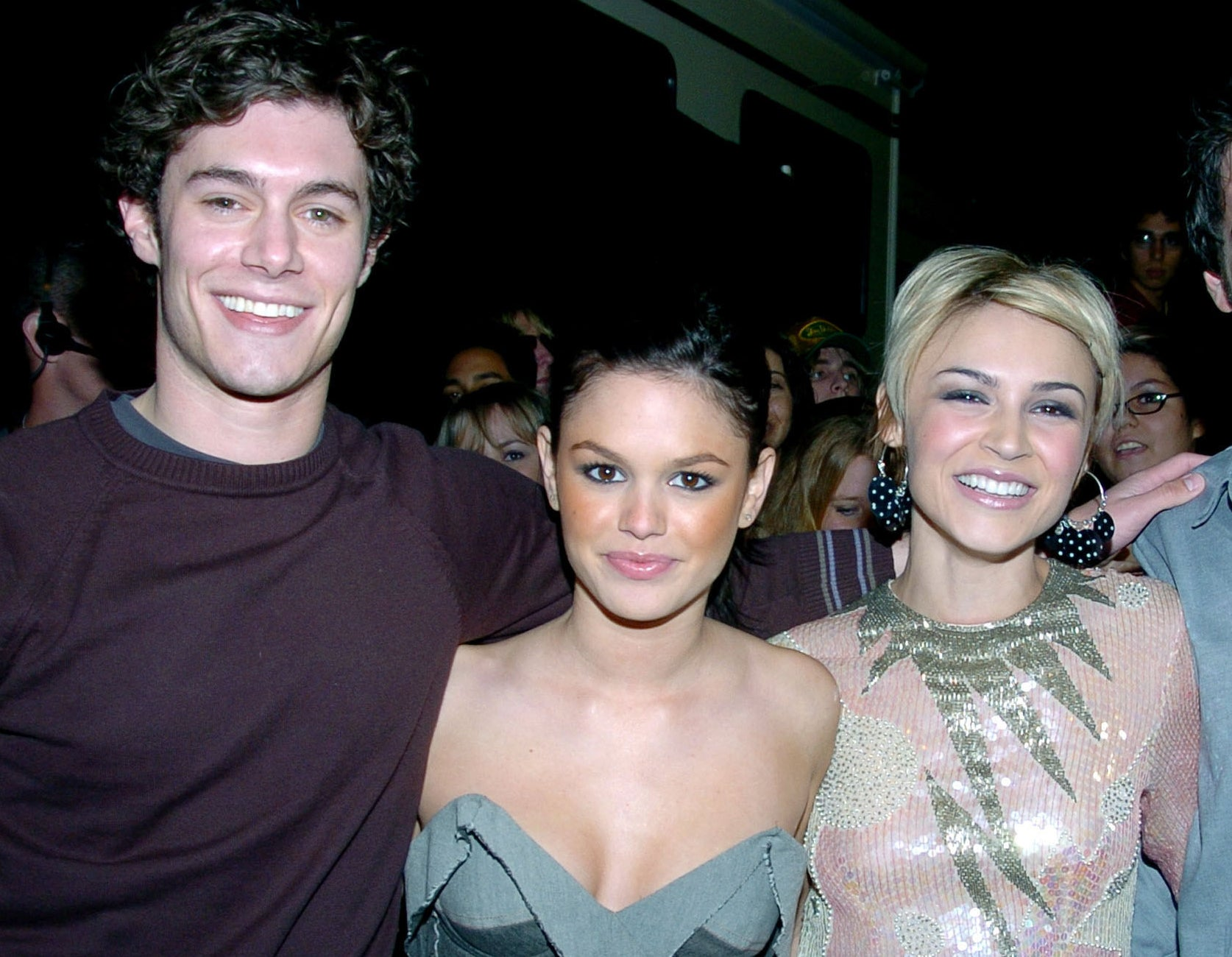 Adam smiles while standing next to Rachel and Samaire