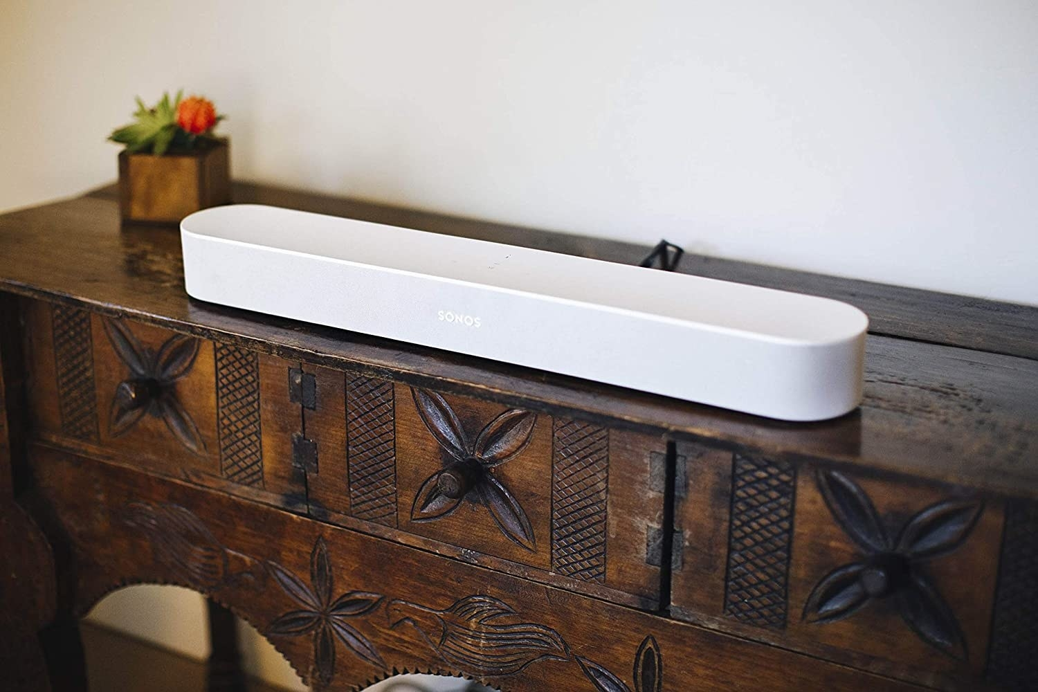 A long sound bar on a wooden TV stand