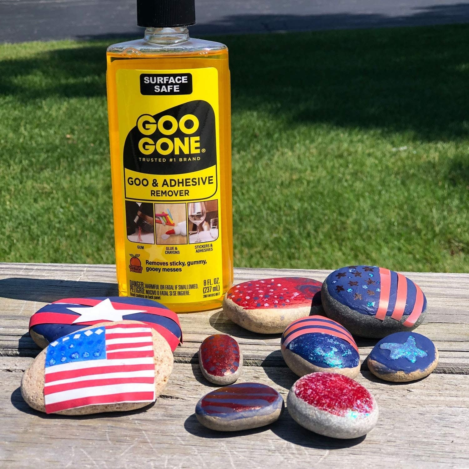 A bottle of adhesive remover next to a bunch of painted rocks
