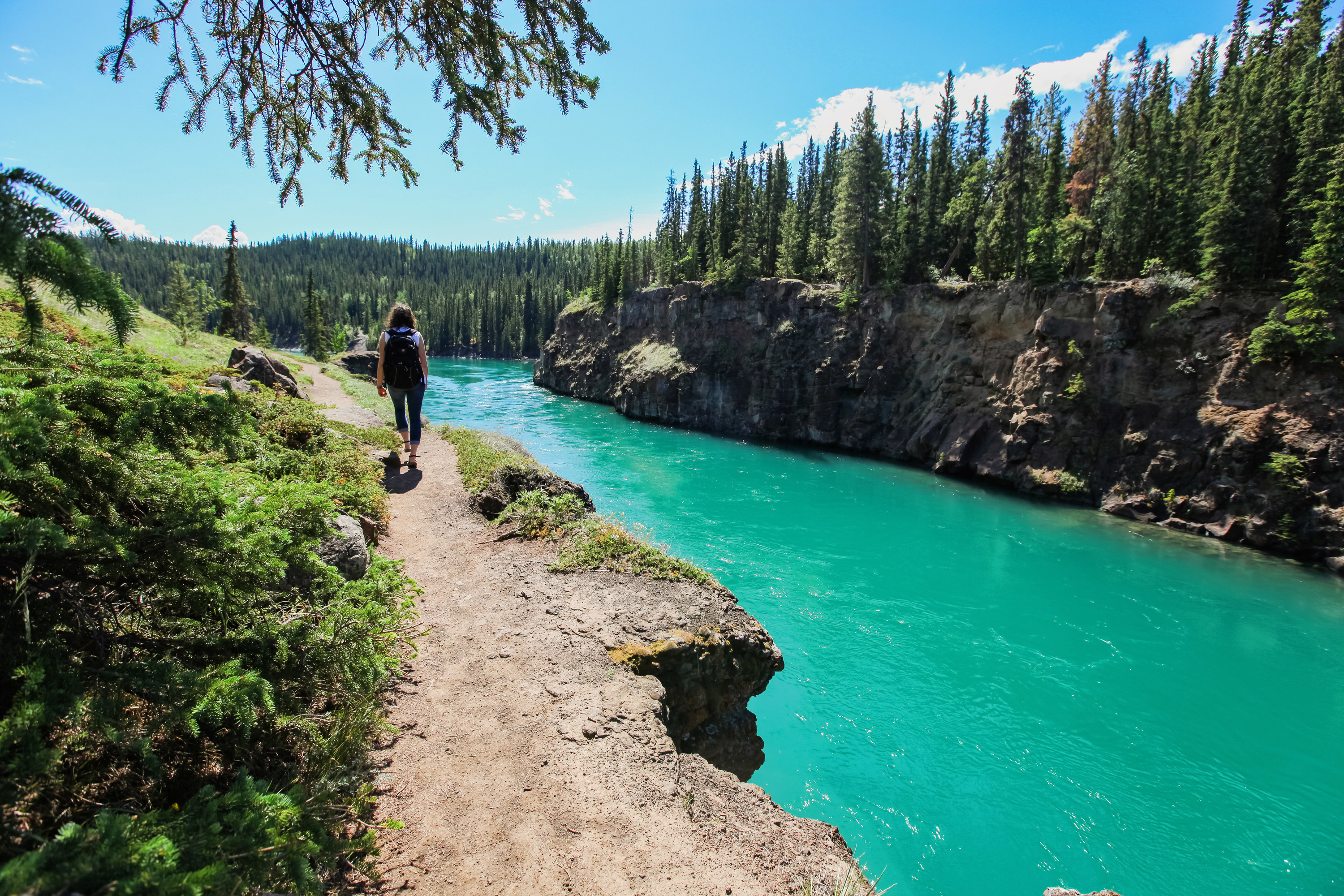 A hiker passes alongside Miles Canyon in the Yukon