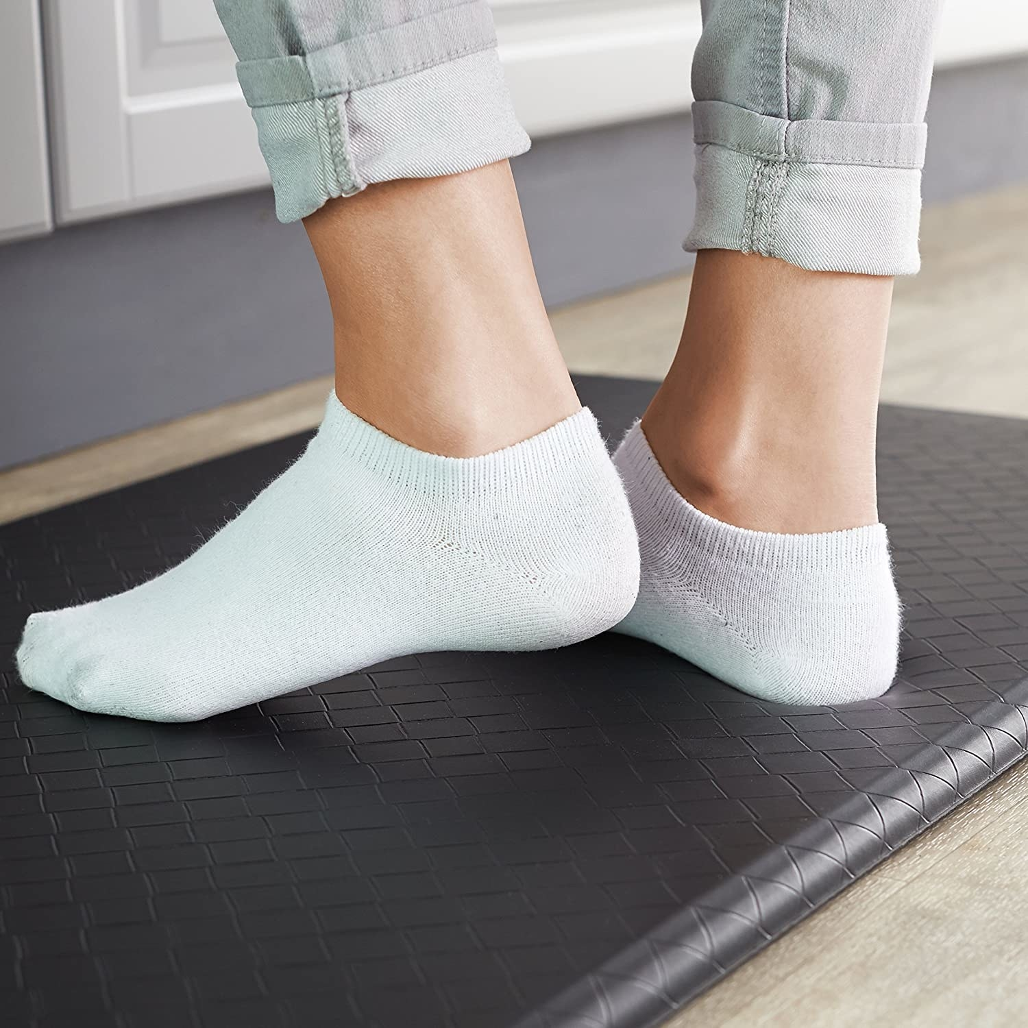 A person standing on a cushy mat in their kitchen